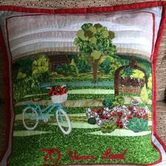 70th birthday cushion for a much loved lady. Designed and created from photos of her garden, strip pieced scenery with appliquéd hedge, tree, garden seat arbour, sunken garden with bird bath and a garden shed in the background. Her bicycle was appliquéd to the foreground and silk ribbon flowers added in keeping with the red theme. Designed and created by Susan Elmore November 2016