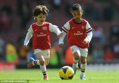 Child's play: Sagna and Arteta's sons have a kick around - careful they're young enough for Arsene to sign them up lol