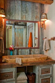 The rustic bathroom sink is made from an antique wooden Indonesian bread  bowl that the couple brought from their previous home. Look in the mirror to see a barn door crafted of reclaimed wood and metal.
