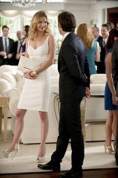 Emily VanCamp wears a white cocktail dress with nude peep-toe pumps, a chunky gold bangle, and a white envelope clutch