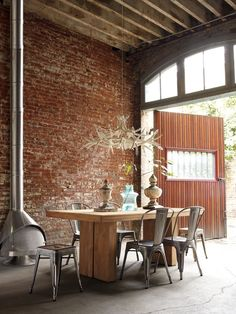 Stunning rustic industrial dining space. Exposed brick, replica tolix, stainless steel fireplace and that amazing timber door!