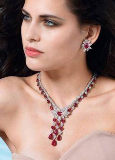 Los colores de el collar y unas aretes son plata y rojo. Los aretes y collar de rubíes tienen sobre ustedes.