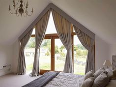 Curtains in a large apex window by Hampshire Curtain Makers.