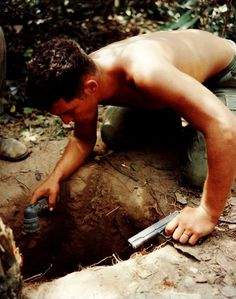 Tunnel Rat, 1967. Flashlight and .45 pistol in hand, a squad leader from the U.S. Army 25th Infantry Division searches for the enemy in an underground tunnel in Củ Chi, northwest of Saigon.