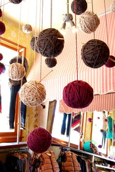 Christmas window display ideas. Wrap colored or metallic yarn around styrofoam balls and hang like garland? Or in window?