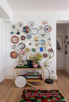 Parede com muitos quadros decorativos e carrinho de chá com obra de arte e vasos de plantas.