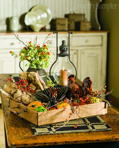 This rustic autumn centerpiece features a lantern, a redware rooster and a pewter pitcher of greenery in addition to gourds and vines that add life.