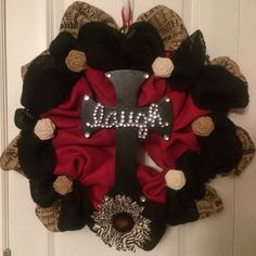 Burlap cross wreath in red, black, natural with black cross that says Laugh. Burlap also has live, laugh, love on it.
