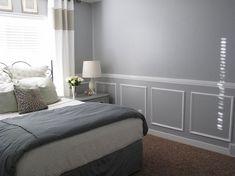 Weiße Wandkasetten aus Stuck in einem grauen Schlafzimmer