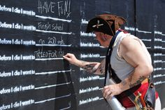 """the corner of Marigny and Burgundy in New Orleans into a giant chalkboard featuring a sort of public """"bucket list."""" A prompt at the top reads """"Before I die..."""", and in blank spaces below, passersby can use the provided chalk to fill in the things they want to do before they expire. Have you been to this???"""