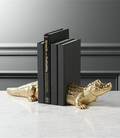 Shop Set of 2 Alligator Bookends. Gilded gators prop tales with true-to-life reptilian details and a hint of humor. Cast in polyresin, sculpture shines in gleaming gold. Fun as decor. Even better as a gift. alligator bookends set of two is a exclusive. Mini Arcade Machine, Modern Bookends, Cloud Lamp, Diy Cloud, Home Decor Mirrors, Tealight Candle Holders, Candleholders, Modern Sculpture, Office Gifts