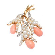Elegant and feminine, this beautiful estate brooch showcases beautiful white round freshwater pearls, complemented by pear-shaped coral accents and sparkling white diamonds. Secured with a barrel clasp, this brooch is crafted of warm 18k yellow gold.