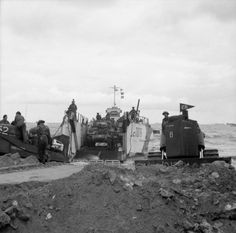 Sherman tanks of 'A' Squadron, Nottinghamshire Yeomanry (Sherwood Rangers), 8th Armoured Brigade, come ashore from a landing craft (LCT 1076) on Jig beach, Gold area, 6 June 1944. On the right, a bulldozer helps clear a path off the beach.
