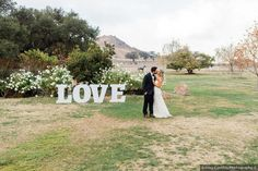 Wedding photography in front of white 'LOVE' sign