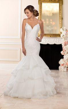 Perfect for the bride who wants it all, turn your dreams into a reality with this princess wedding dress from Stella York. Showing off your curves effortlessly, the drop-waist bodice of this gown features bold lace detailed with latticework that is perfectly complemented with a plunging V-neckline and shoestring straps. A tiered, tulle skirt gives a dramatic effect to this princess wedding dress while creating an enviable trumpet silhouette. The back of this glamorous gown features an…