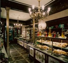 Pastelería El Riojano. Fue fundada en 1855 por el pastelero personal de la Reina María Cristina de Habsburgo, Dámaso Maza, oriundo de La Rioja, de ahí el apodo con el que se le conocía y que da nombre al establecimiento. El local presenta la típica fachada de los comercios del siglo XIX, donde se combinan la madera, el mármol, los escaparates de cristal y el elegante rótulo que da nombre al local.