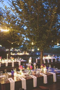 Create a romantic atmosphere for your outdoor wedding reception with hanging candles and florals.