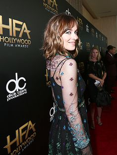 All the Must-See Photos from the Hollywood Film Awards | OVER THE SHOULDER | Wearing a lacy black dress adorned with shimmering flowers, Dakota Johnson adds some intrigue to the parade of arrivals.
