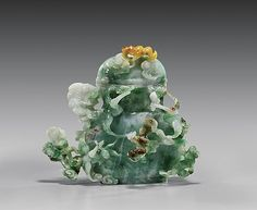 """CARVED JADEITE COVERED VASE Chinese carved jadeite vase and cover; of flattened form, with design of cranes and bats amid swirling clouds in delicate openwork relief; the translucent jadeite with some bright green lavender and russet coloration; H: 5 1/4"""""""