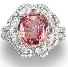 A padparadscha sapphire and diamond ring. Set with a cushion-cut padparadscha sapphire, weighing 5.23 carats, within an openwork double-tiered surround of marquise and round brilliant-cut diamonds, between diamond-set split shoulders, mounted in 18k white gold, the diamonds estimated to weigh approximately 1.40 carats in total, ring size 6¾. Via Bonhams.
