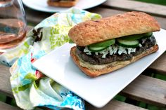 Lamb burgers loaded with fresh herbs and topped with hummus, feta, cucumber, and avocado.