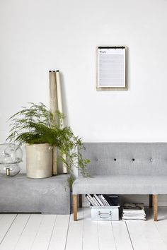A slim grey sofa perfect for an office corner with piles of magazines and plants