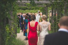 Bride and bridesmaid walking through the arches at Coworth Park Wedding - Maria Assia Photography. http://mariaassia.com/coworth-park-barn-summer-wedding-photography/