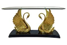 Brass Swan Console Table on OneKingsLane.com described by Erin Giglia Design Stunning console table featuring a pair of brass swans, with a lovely even patina, supporting a beveled glass top with applied brass moulding. Minor wear to the black lacquered base that has been retouched. No maker's mark.