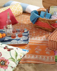 This outdoor use of patterns could work well indoors, too. There are so many patterns at play here: a floral, butterfly print, the pink woven acrylic, a sunny ikat pillow, a nautical stripes pillow, and an orange houndstooth seat cushion.