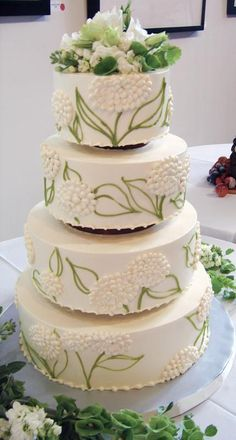 Love the design on this wedding cake and matching flowers surrounding the base