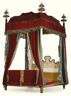 A German baroque velvet and silk embroidered state tester bed, first half of 18th century is covered in red silk velvet and topped by finials and tassels, the shaped headboard covered with floral silk embroidery in cream ground with roundels with oriental style birds, footboard covered with velvet, one hanging with the embroidered Spee monogram, the posts with blue silk and red velvet hangings