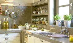 Uma cozinha organizada toda cinza, em cimento