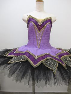 NEW COLLECTION 2015! This is a fantastic stage costume, exclusively presented by Dancewear by Patricia. The bodice of this tutu is deep lilac and features a deeper violet inset and rich gold decoratio