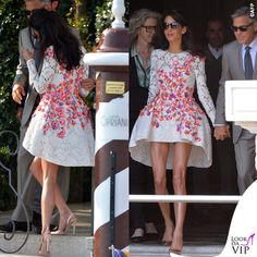 Il giorno dopo le nozze Amal Alamuddin, o per meglio dire la tanto attesa Mrs Clooney, indossa un abito Giambattista Valli, asimmetrico e rigido, in pizzo bianco con fiori rossi e viola.