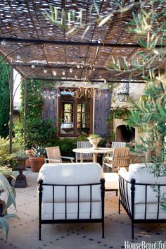 A chandelier and string of lights add even more romance to the patio of a Corona del Mar, California, house designed by owner Dana Abbott and her design partner, Kim Fiscus. A simple grid of black river rocks add an elegant detail in the concrete patio. Outdoor Rooms, Outdoor Gardens, Outdoor Living, Outdoor Furniture Sets, Outdoor Decor, Deck Furniture, Outdoor Seating, Outdoor Landscaping, Backyard Patio
