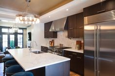 The open plan kitchen mixes sleek efficiency with luxurious stylings: Blue velvet dresses up the round barstools, the backsplash and countertops are white marble. Stainless steel, high-end appliances keep the chef happy.
