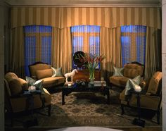 SUZANNE MYERS ELITE INTERIOR DESIGN: Dramatic lighting, sensuous silk sheer drapery panels, Pakistani Oushak Design area rug, and four over-stuffed French Regence lounge chairs surround a custom black Chinoiserie coffee table.