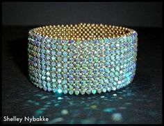 I think I could make this with right angle weave base and overlaying crystals woven on top, similar to the lattice bracelet I made, but tighter weave and closer together. However this one does not appear to have a clasp, so I assume it is a bangle which slips over the hand