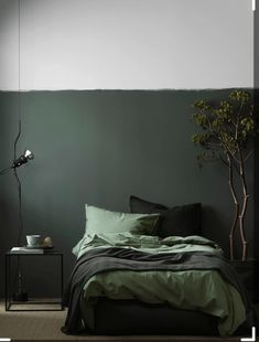 """Swedish interior stylist Pella Hedebycreated this moody olive bedroom for Elle Decoration Sweden. """"The grayish-green wall color is Dark Paris from Nordsjö and the Stonewashed Cotton Bed Set is from Artilleriet,"""" she tells us. See more of Hedeby's work at her blog Still Inspiration. Photograph by Ragnar Omarsson."""