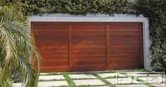 Mid Century architecture calls for minimalistic basic design crafted with high quality to last a lifetime. This African Mahogany handcrafted garage door's design is minimalistic yet rich in quality that is evident in its design. The rich hand-stained variations in the tongue and groove wooden planks demonstrate the beauty of natural wood variations even within …