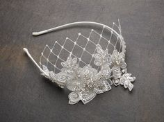 This ravishing Vintage Lace Headband with an alluring touch of Wide Net Veiling is reminiscent of the fabulous Art Deco style of wedding design. This heavily crystalled lace applique has a slender sat