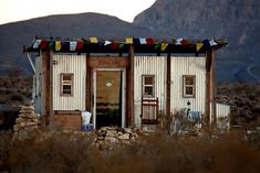 John Wells built the shell of this one-room shack over nine days in 2007; now his 60-acre homestead, deep in the West Texas desert, includes four shipping containers under an arched metal roof, nine water tanks, a solar shower and a solar oven.