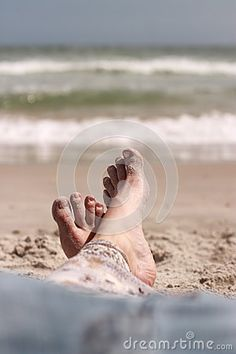 sandy toes rest on the sand as the ocean  waves play in the background.