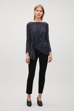 This top is made from a comfortable cotton jersey with a subtle shine and pleat detail at the front. An A-line fit, it has short sleeves, a round neckline and raw-cut finishes.