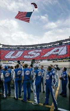 Kurt Busch's crew watches as a paratrooper brings the American flag into the track prior to the Aug. 2006 race. (Mark Humphrey/AP)