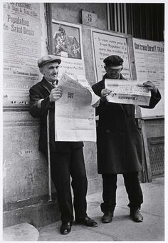 Men reading newspapers the day of the election run-offs that would bring victory for the Popular Front coalition government, Saint-Denis, near Paris, May 1936//Robert Capa