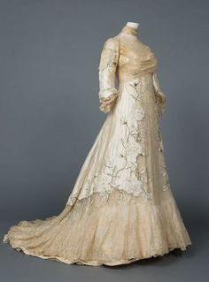 Evening gown, c. 1900   The trained evening gown is of ivory silk taffeta and chiffon with ecru lace insertions, applied chiffon flowers embroidered with silver thread and hundreds of vertical pin tucks. But the most striking element is the thousands of dazzling silver sequins that cover the gown in vertical rows.