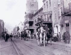 Lt. Col. J. B. Richardson riding his white horse with band parading down Camp Street, New Orleans  (St. Patrick's Church can be seen in the distance.)    circa 1890s
