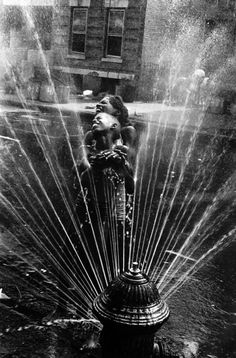 The fire hydrants were opened during the summer heat, Harlem USA, NY, 1963. Photo by Leonard Freed.
