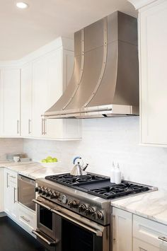 Attractive A Stainless Steel French Kitchen Hood Accented With Rivet Straps Stands  Over A Stainless Steel Stove